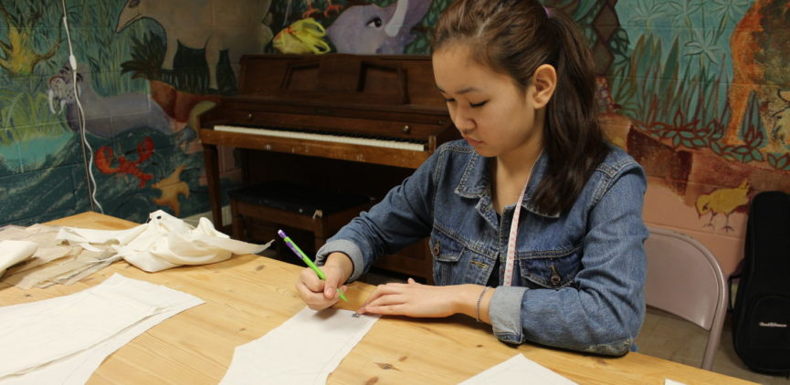 A teen who is interested in costume design, is marking out a pattern for a new design.
