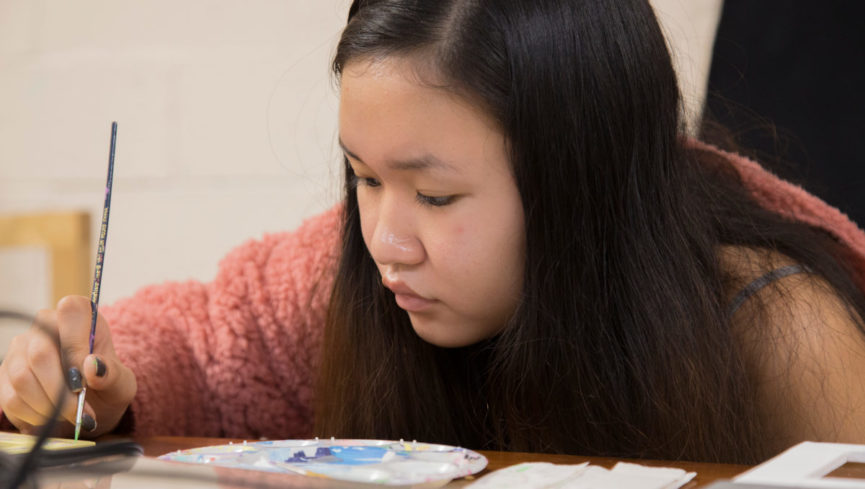 A girl focused on creating a painting