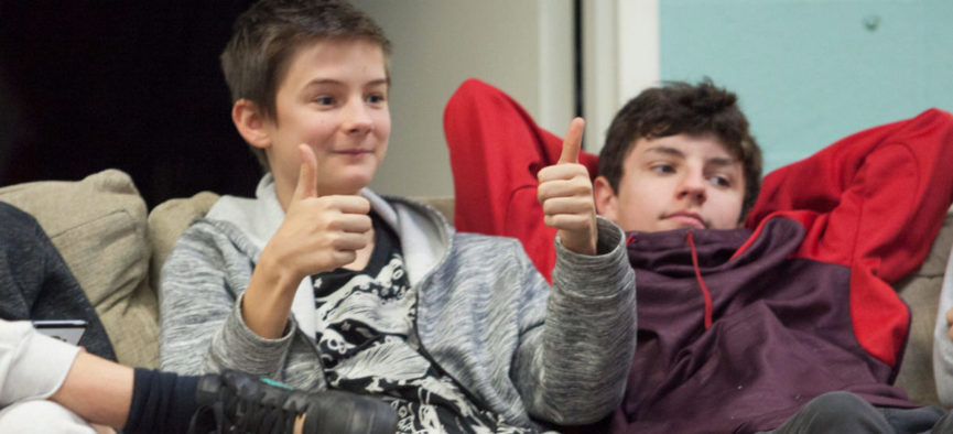Two boys sitting on a couch at PLC, one leaning forward with two thumbs up, the other lounging back