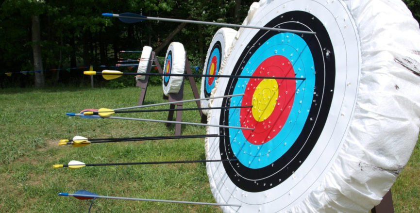 a row of archery targets with arrows stuck in them