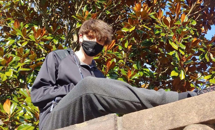 Masked teen sitting on the wall behind Bucks center, enjoying a sunny warm day in march.